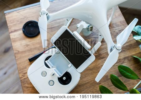 A fresh spring photo of a drone with a control panel on the background of a wooden table and a green plant. Aerial shooting concept. Before flight training. Top view. Outfit before the flight.