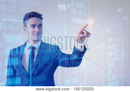 Future technology concept. Pleasant young businessman is sending messages by pressing button on virtual touchscreen. Copy space in the right side