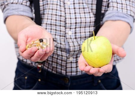 Idea of proper nutrition and treatment. Mans hands hold green apple and handful of pills or fish oil capsules. Guy with fresh fruit on white background. Healthy lifestyle and diet concept