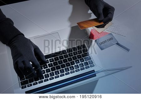 Payments system hacking concept. Close up top view of hands of unknown man wearing black gloves. Hacker is cracking pin code of credit card using laptop