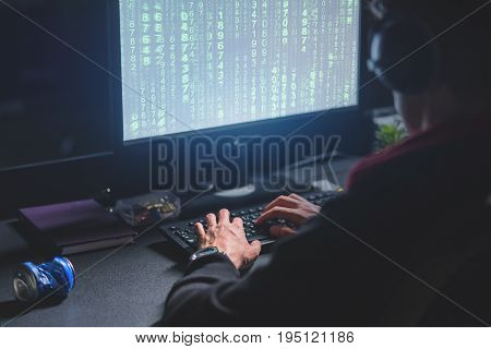 Decoding information. Back view of involved experienced hacker is sitting in dark lighted room and working on computer while typing on keyboard
