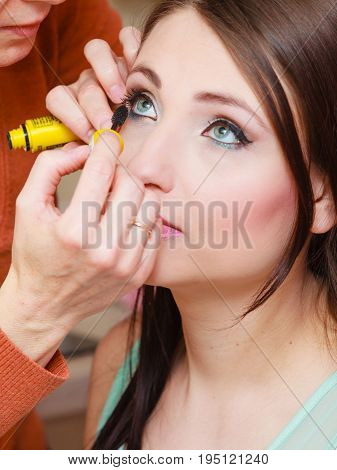 Visage female beauty concept. Woman getting her eyelashes makeup done by professional artist.