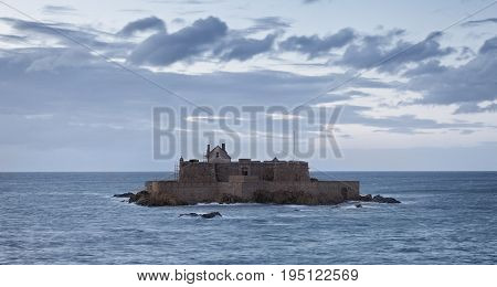 Dusk image of The Fort National from Saint Maloin Brittany in northwestern France during the high tide time.The construction was used first as a reference point for the ships and from 1869 became a defensive bastion against the English attacks.