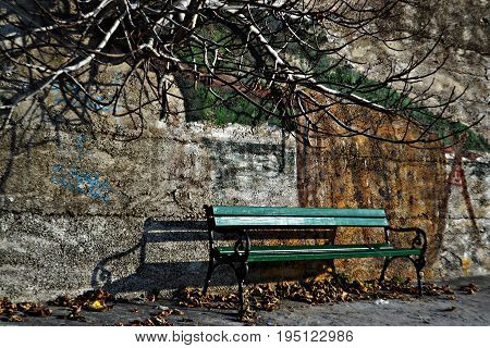 Green bench whit wall graphite as background