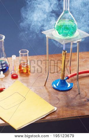 Bunsen burner heating flask with science equipment in laboratory