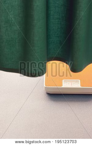 Weighing scales under curtain in hospital