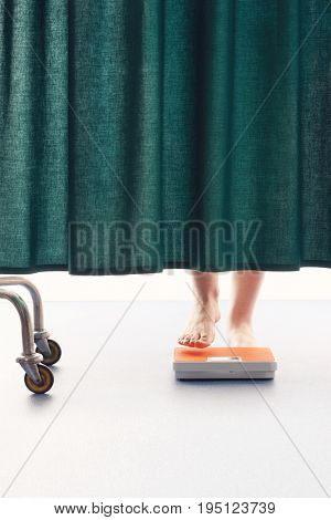 Person stepping onto weighing scales behind curtain in hospital