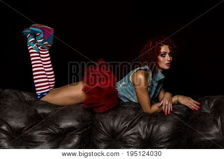 Curly redhead sexy girl sits on a leather sofa. Girl looks like a doll for adult men. Fashion style.