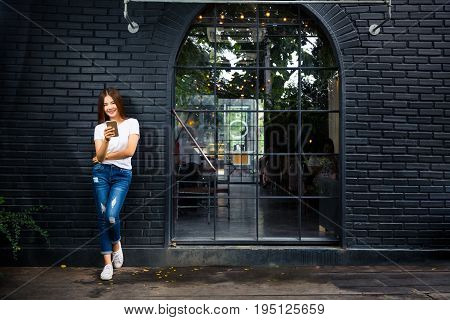 young happy woman standing leaning against dark brick wall outside a coffee shop using her phone concept of young hipster generation lifestyle using technology