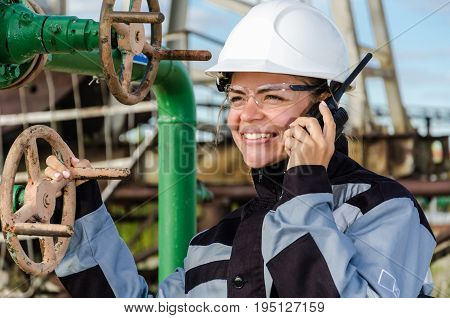 Woman engineer in the oilfield talking on the radio wearing white helmet and work clothes. Industrial site background. Oil and gas concept.