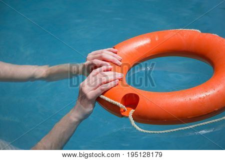 Close up of woman hands holding lifebelt in sea. Emergency drowning help concept