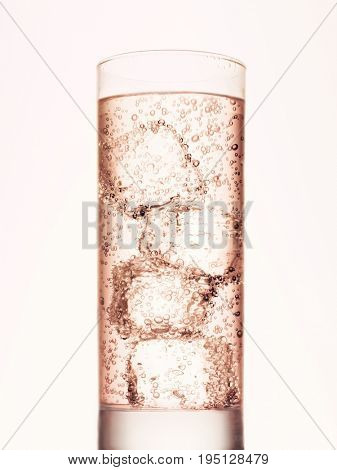 Brownish drink with ice cubes on white background