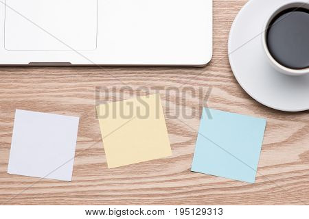 Laptop with colorful stickers on wooden table.