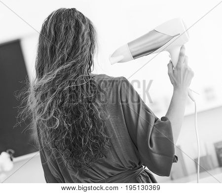 Young Woman Blow Drying Hair In Bathroom . Rear View