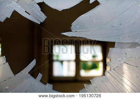 Broken Window Glass looking inside a House with a window background opposite site