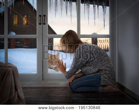 The girl looks through the window at the cat. The house is warm. The street is cold cat. Cold winter snow