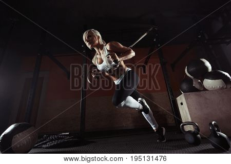 Fitness woman workout on the TRX in the gym. Fitness woman workout on the gym. Fitness woman in the gym. Training TRX straps. TRX gym