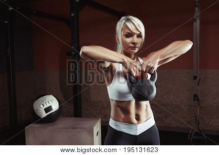 Fitness woman doing a weight training by lifting kettlebell. Muscular fitness woman, holds up a black kettlebell in the gym. Fitness woman in the gym.