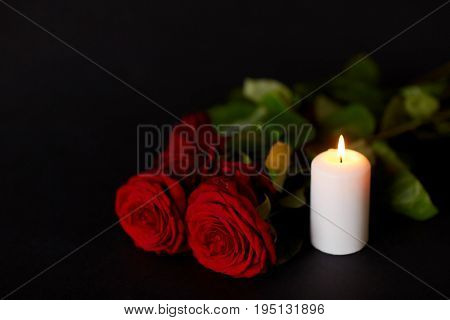 funeral and mourning concept - red roses and burning candle over black background