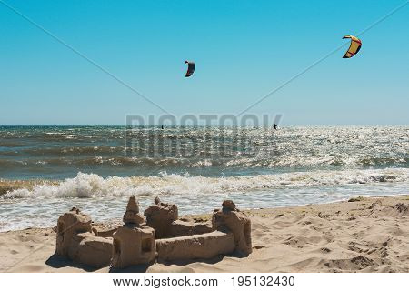 Two kitesurfs in the sea against the background of the blue sky. In the foreground sandy castle on the shore.