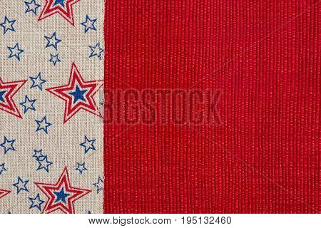 Red and blue star burlap ribbon on a shiny red material on a shiny red material with copy space for your message