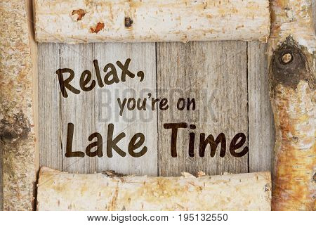 Relax you're on Lake Time text on weathered wood with birch log frame