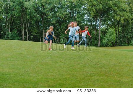 Happy Multiethnic Kids Playing Together And Running On Green Grass In Park