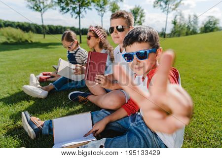 Multiethnic Kids In Sunglasses Reading Books And One Boy Gesturing At Camera