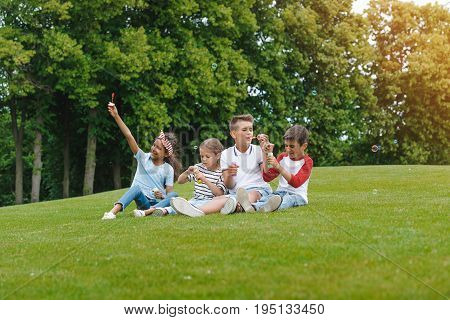 Happy Multiethnic Children Sitting On Green Meadow And Blowing Soap Bubbles In Park