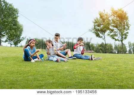 Adorable Multiethnic Kids Blowing Soap Bubbles While Sitting Together In Park
