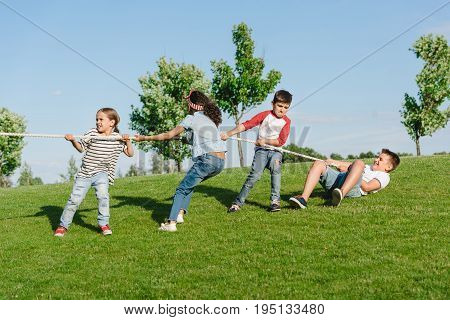 Cheerful Multiethnic Kids Pulling Rope And Playing Tug Of War In Park