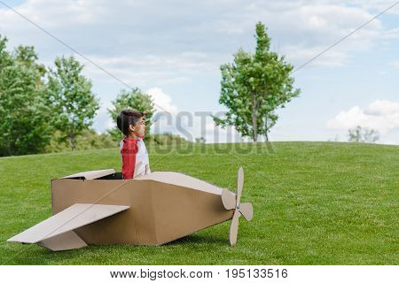 Cute Little Boy Sitting In Cardboard Toy Plane And Looking Away In Park