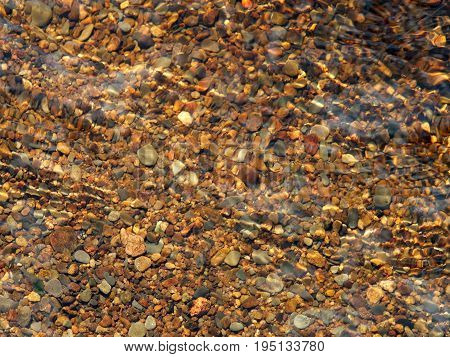 mixed brown pebbles in a riverbed with ripples on the water