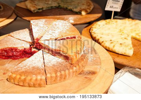 Sliced various pies at food market. Pieces of cut-up fruit pie