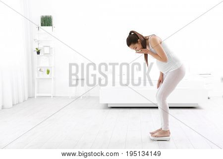 Pregnant woman standing on scales at home. Pregnancy weight gain concept