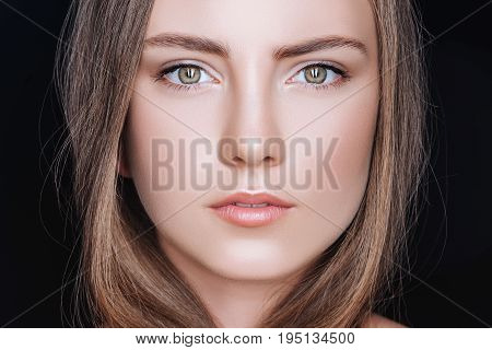 Portrait Of Attractive Young Woman With Neutral Makeup Isolated On Black