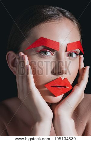 Portrait Of Woman With Red Paper Lips And Brows On Face Posing For Fashion Shoot Isolated On Black