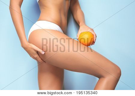 Young woman holding orange on color background. Cellulite problem concept