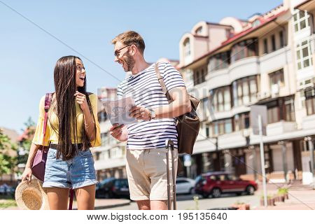 Cheerful Young Multiethnic Couple Of Tourists Holding Map And Smiling Each Other