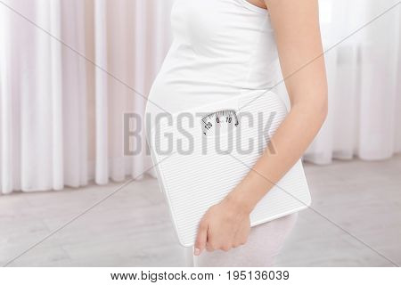 Pregnant woman with scales at home. Pregnancy weight gain concept