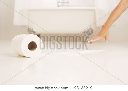 Cropped image of woman's hand reaching tissue paper in bathroom