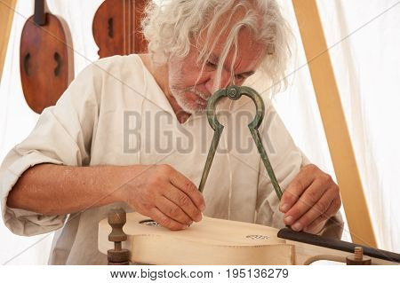 Luthier working on the creation of a stringed instrument. He uses a large compass to take the exact measure