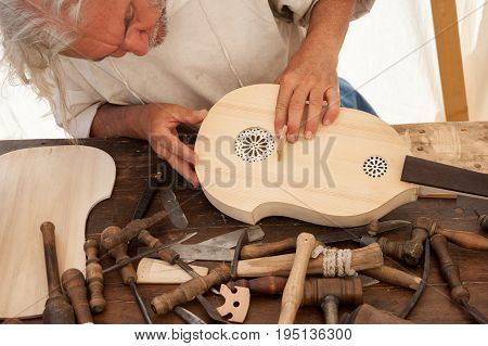 Luthier working on the creation of a stringed instrument. Various tools and instrument are placed on the workbench