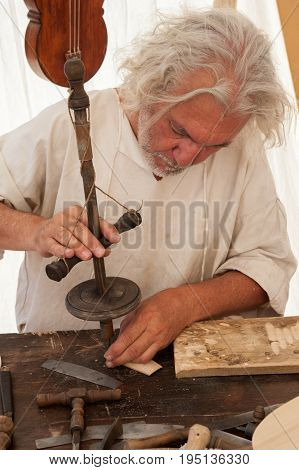Luthier working on the creation of a stringed instrument. He uses an old manual drill