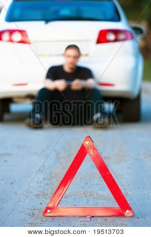 Car accident on a road. Focus is on the red triangle sign