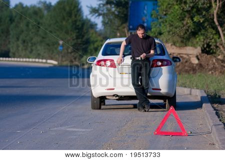 Young man sends an sms standing by a white car