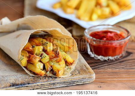 Crispy potato fries. Oven baked sweet potato fries in paper and white plate, tomato sauce. Wooden table. Rustic style. Closeup