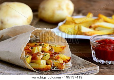 Spicy potato fries. Baked sweet potato fries in paper and white plate, spicy tomato sauce, raw potato on a wooden table. Closeup