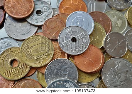 Financial background consisting of coins from many different countries in the metal box as a symbol of international trade and business