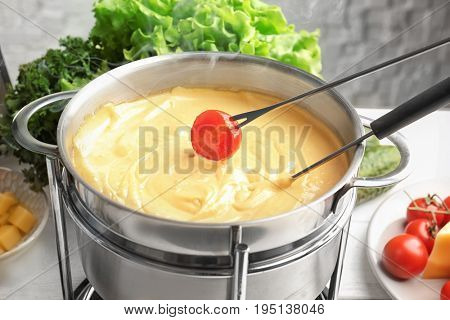Pot with delicious cheese fondue and dipped tomato on table, closeup